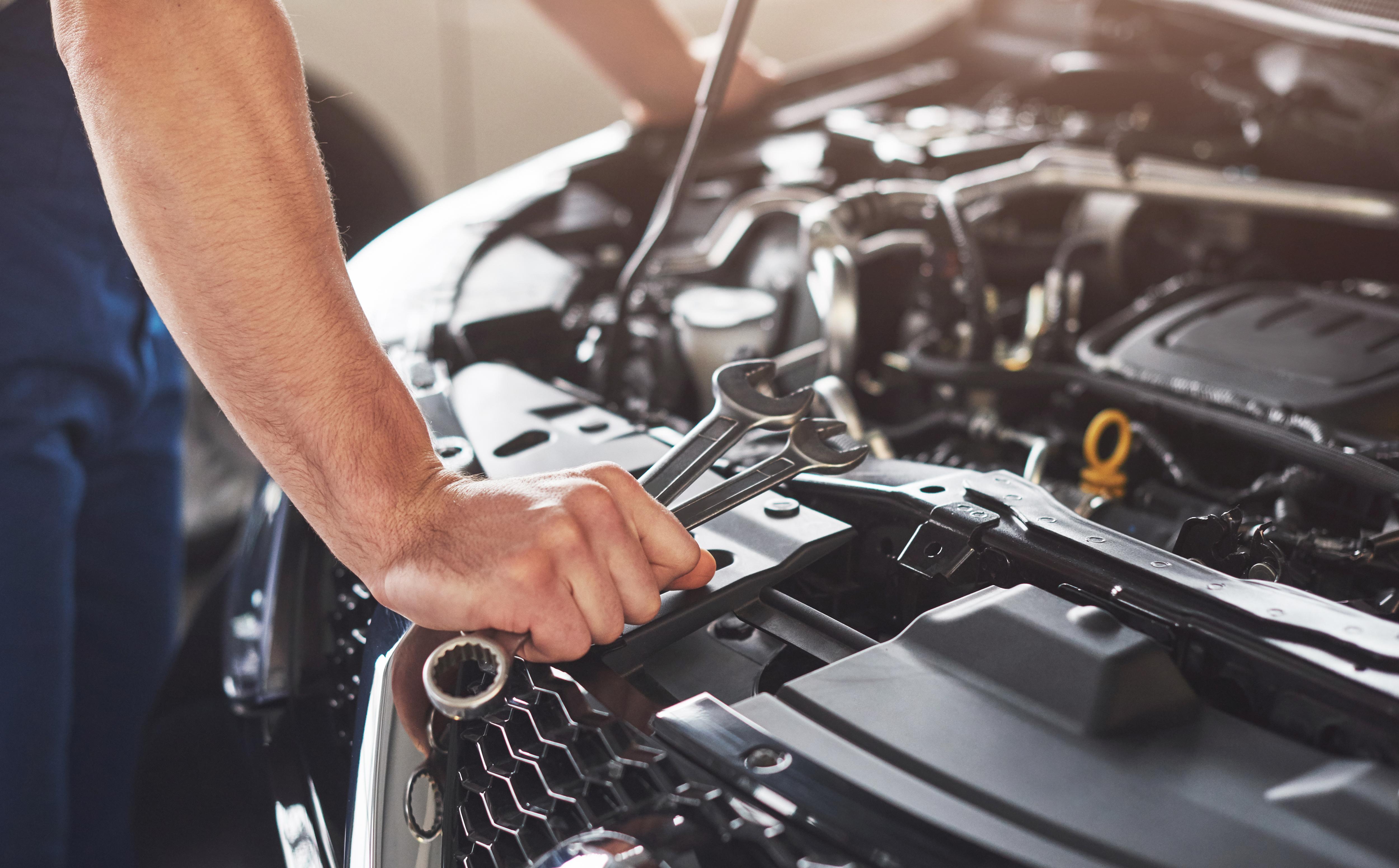 muscular-car-service-worker-repairing-vehicle
